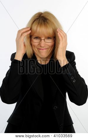 Stressed out office female worker with hands to head and pained expression