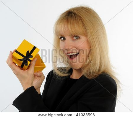 Attractive blond woman opens gift box with surprised expression