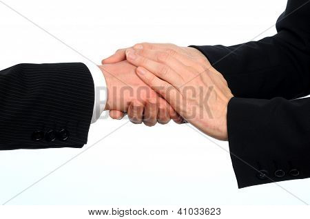 closeup image of male and female executives shake hands on deal with woman putting second hand on to