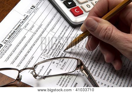 View of United States tax form with hand holding sharpened pencil with calculator and glasses