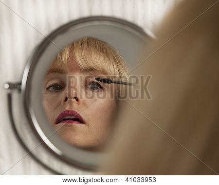 Attractive blond woman applies eyeliner makeup in mirror
