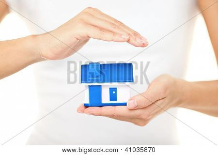 Home insurance. Woman holding a model house in one hand while forming a protective covering with the other conceptual of home insurance and protection