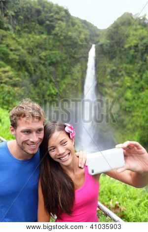 Tourists couple taking self portrait photo on Hawaii with camera phone on Hawaii, Big Islands, Akaka Falls. Happy cheerful young multiethnic couple on travel.
