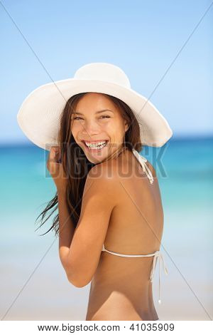 Asian woman beach portrait. Happy lifestyle photo of mixed race Asian Chinese / Caucasian young lady in bikini smiling pretty wearing beach hat on summer holiday vacation.