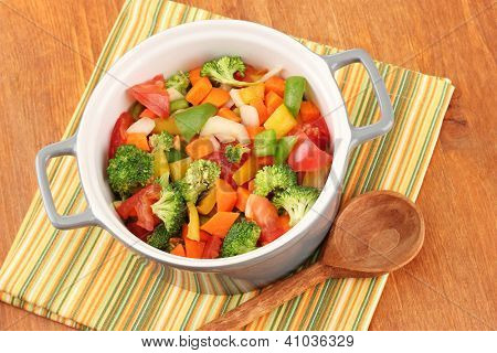 Vegetable stew in gray pot on color napkin on wooden background