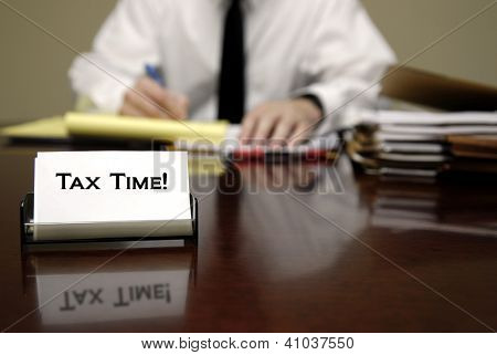 IRS tax auditor man sitting at desk with business card