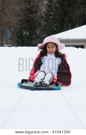 East Indian Girl Toboganning In The Snow