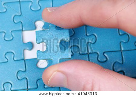 Fingers Holding A Puzzle Piece