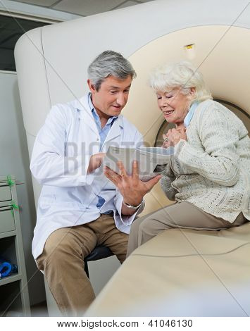 Mature male doctor with a book explaining to senior female patient