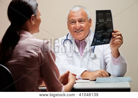 Senior male radiologist smiling while showing x-ray to female patient
