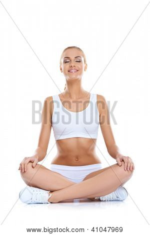 Serene happy woman with a shapely figure and bare midriff sitting cross-legged on the floor meditating, studio portrait over white