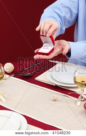 A man proposing and holding up an engagement ring over restaurant table