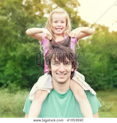 Young Man Holding Blonde Little Girl On Shoulders In Park In Summer