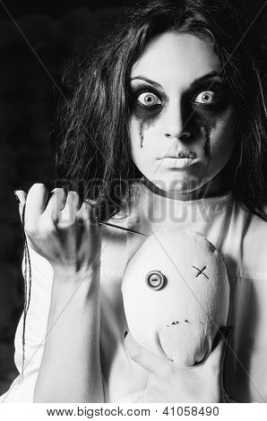 Horror Scene: The Strange Crazy Girl With Moppet Doll And Needle In Hands. Closeup