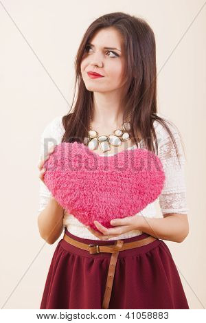 Young girl in love holding gift fluffy heart in hands