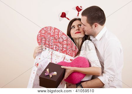 Couple in love hugging on valentines day while girl is holding presents
