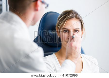 Optometry concept - pretty young woman having her eyes examined by an eye doctor/optometrist (color toned image; shallow DOF)