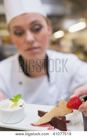 Chef putting strawberry on dessert plate in the kitchen