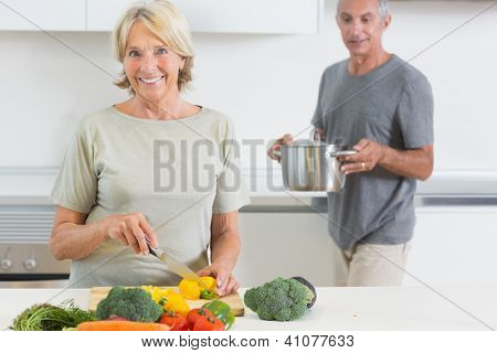 Husband bringing a pan to his wife in the kitchen