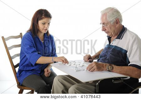 An attractive young volunteer playing Dominoes with an elderly man in a wheelchair.  On a white background.
