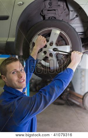 Portrait of male mechanic fixing car tire with wrench in garage