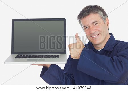 Portrait of happy mechanic with laptop showing thumbs up sign against white background