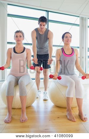 Two women at the gym with dumbbells sitting on exercise balls along with their coach