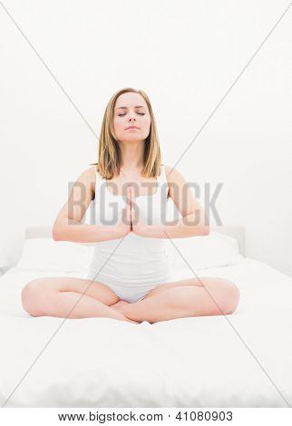 Young woman sitting in praying position with eyes closed on bed at home