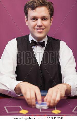 Dealer shuffling cards and smiling