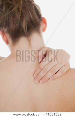 Close-up of topless woman massaging back over white background