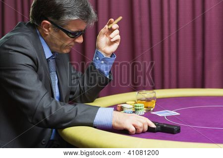 Man wearing sun glasses with gun at poker table in casino