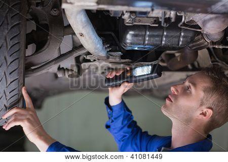 Young mechanic examining car using flashlight