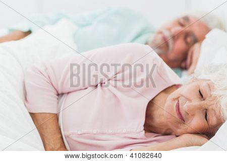 Elderly couple sleeping in bed