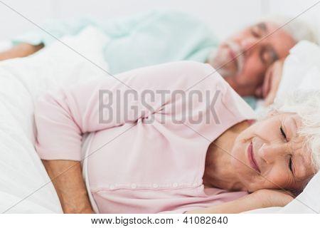 Elderly couple sleeping in bed