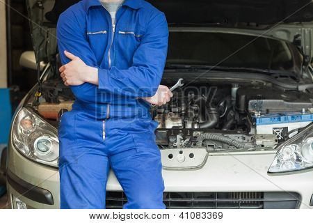 Male mechanic in front of car with open hood