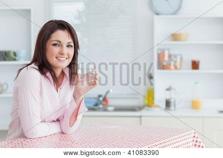 Portrait of young woman with glass of water in the kitchen
