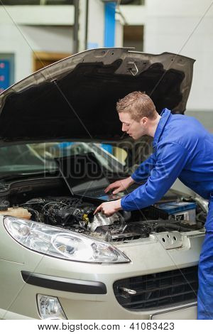 Auto mechanic with laptop repairing car engine in workshop
