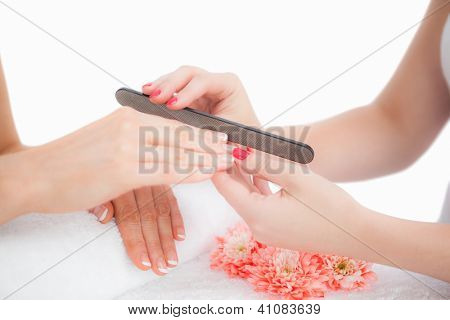 Close-up of woman filing fingernail at nail salon