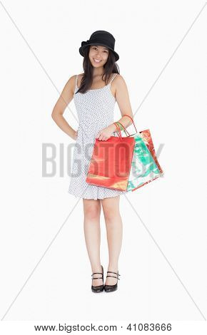 Pretty woman with shopping bags in polka dot dress and hat