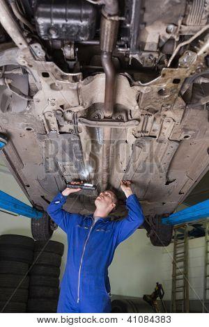 Male auto mechanic examining car using flashlight