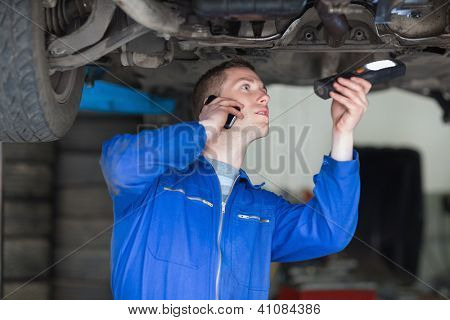 Male mechanic on call while examining car