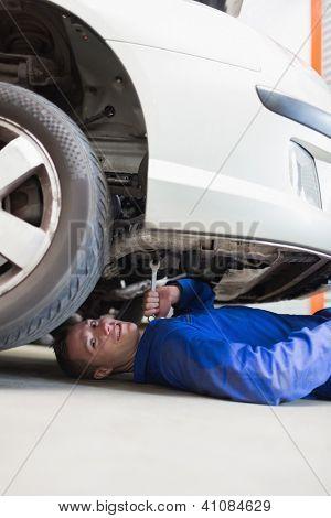 Portrait of male auto mechanic working under car