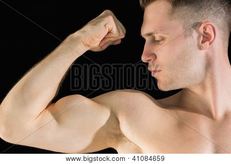 Close-up of young man flexing muscles over black background