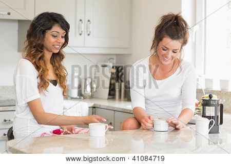 Two friends chatting over coffee at breakfast in kitchen