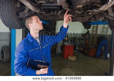 Mechanic with clipboard examining under car in workshop