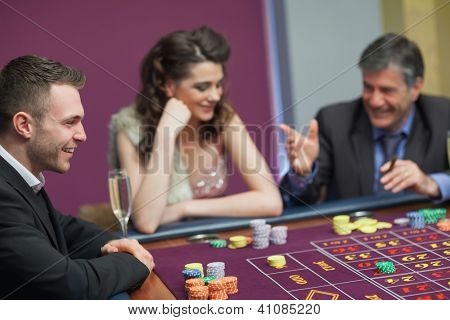 Men and woman talking at craps game in casino