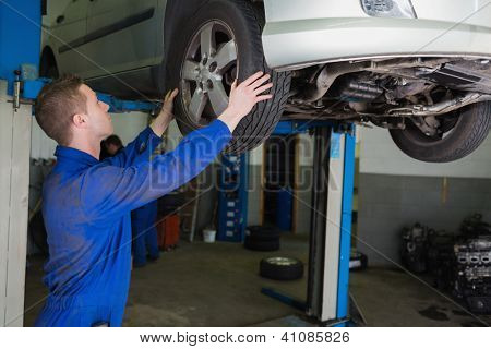 Auto mechanic examining car tire in garage