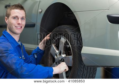 Portrait of young male mechanic changing car tyre