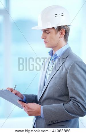 Portrait of businessman in helmet making notes