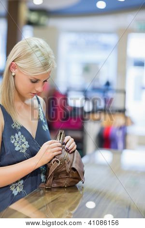 Woman is standing at the counter of the shop while searching in her bag